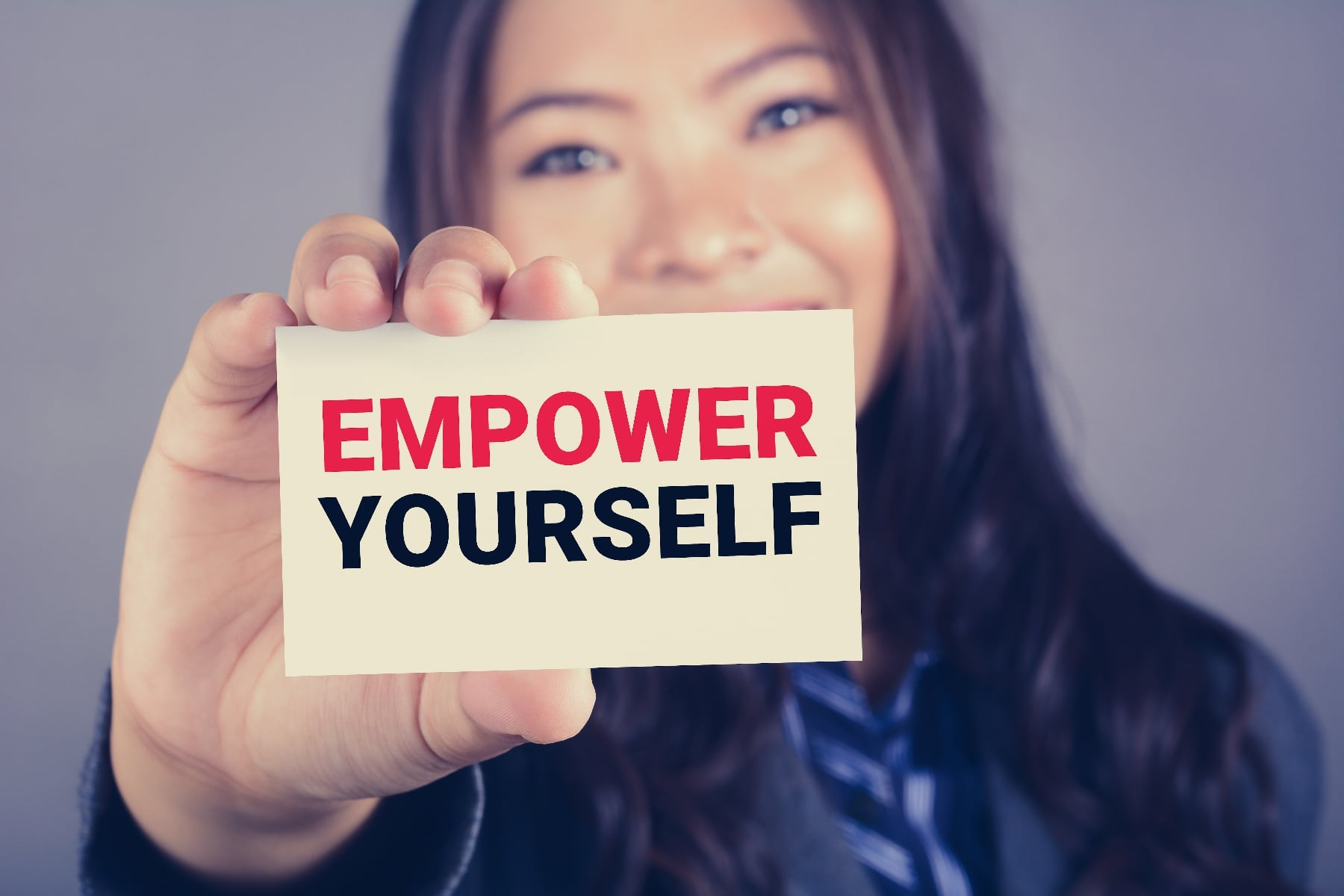 EMPOWER YOURSELF message on the card shown by a businesswoman, vintage tone effect